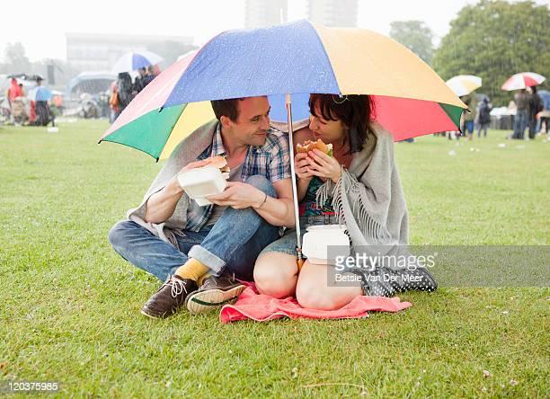 couple hiding under umbrella for rain at festival.