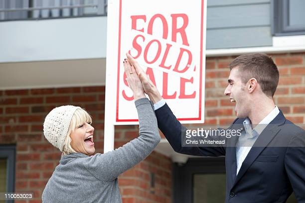 Couple high five in front of apartment