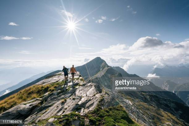 couple hike along a mountain ridge in the bright sun - switzerland stock pictures, royalty-free photos & images