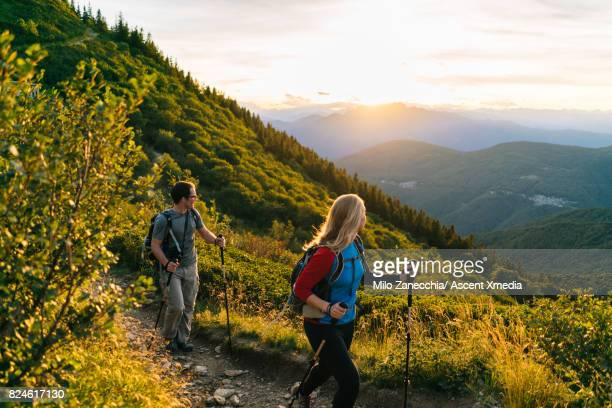 Couple hike along trail at sunrise, mountains