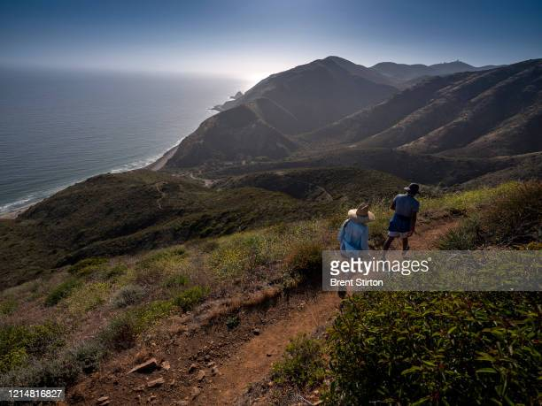 Couple hike through the mountains close to Point Mugu as hiking paths reopen on May 23, 2020 in Ventura County, California. Picnics and groups are...