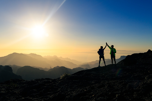 Couple hikers celebrating success concept in mountains 1069988650