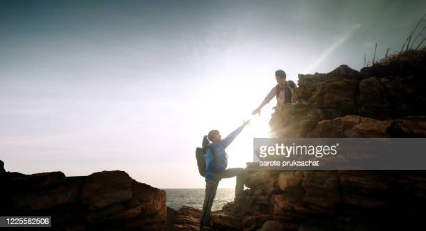 couple hikers climbing up  mountain cliff . helps and team work concept. - trust stock pictures, royalty-free photos & images