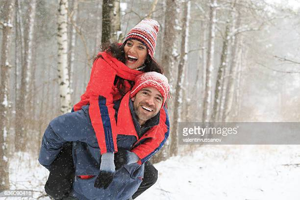 Couple hikers having fun in piggyback ride in snow forest