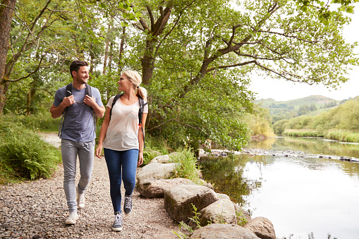 Couple Hiking Along Path By River In UK Lake District 1049852854