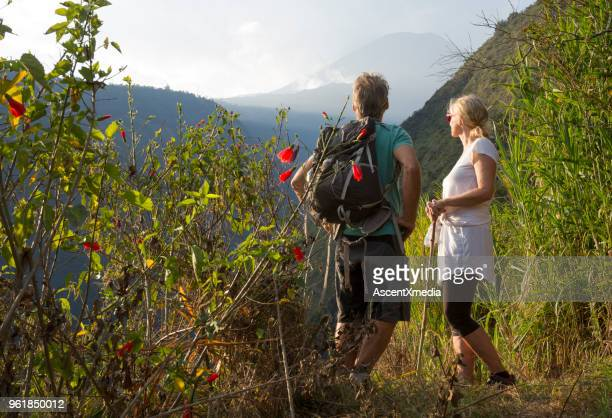 couple hiking below volcano in forest - ecuador stock pictures, royalty-free photos & images