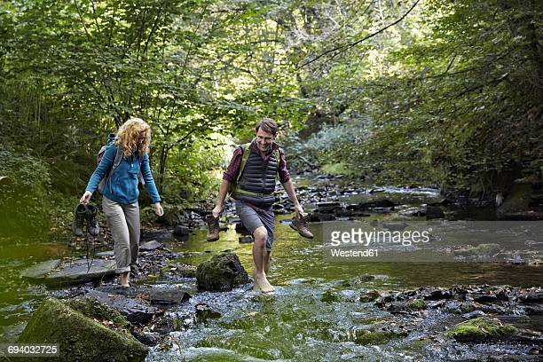 Couple hiking crossing a river