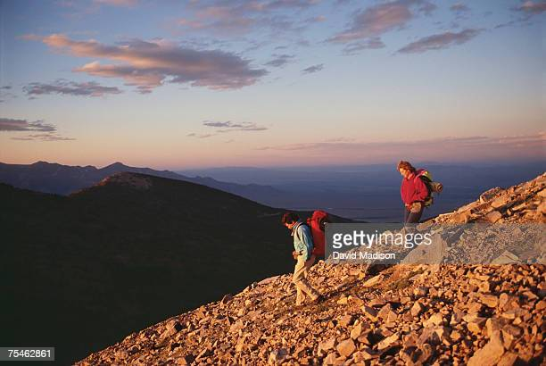 couple hiking down rocky slope in great basin national park, nevada, usa. - great basin stock pictures, royalty-free photos & images