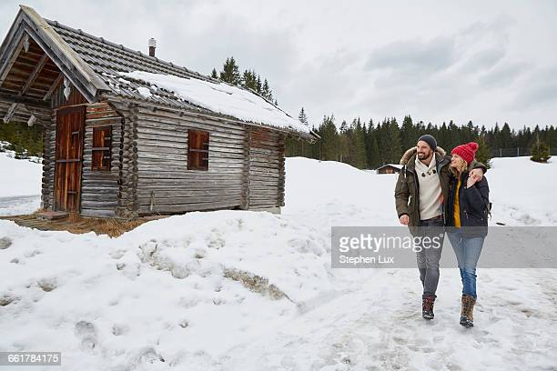 couple hiking from log cabin in winter, elmau, bavaria, germany - parka coat stock photos and pictures