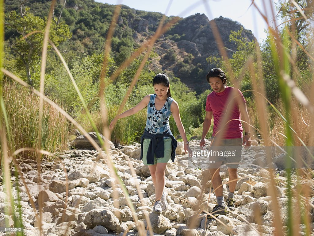 Couple hiking in dry river bed. : Stock Photo