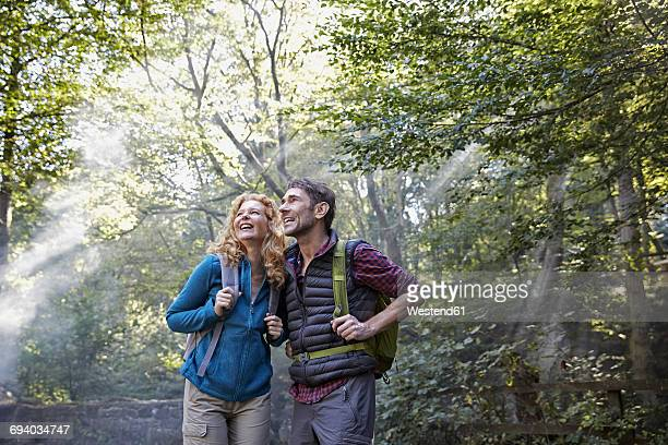 Couple hiking in forest, looking up