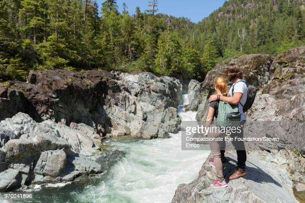 Couple hiking in mountains looking at river view