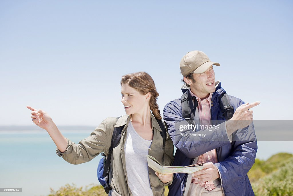 Couple hiking in remote area and looking at map : Stock Photo