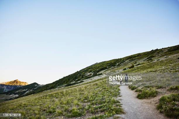 couple hiking on alpine trail at sunrise - clear sky stock pictures, royalty-free photos & images