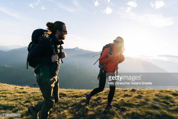 couple hiking on mountain ridge at sunrise, smiling - lifestyles stock pictures, royalty-free photos & images
