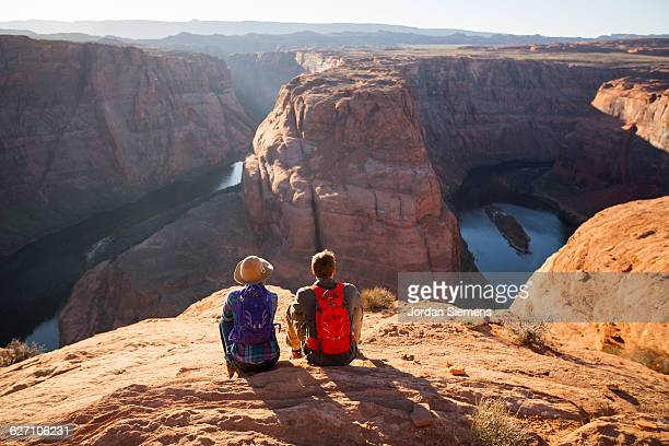 a couple hiking on the edge of a senic overlook. - category:grand_canyon_national_park stock pictures, royalty-free photos & images