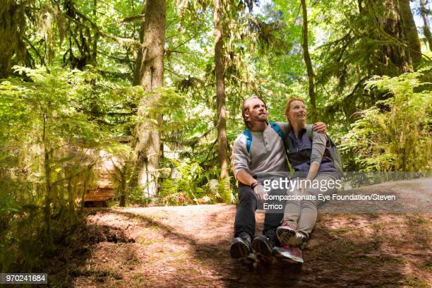 Couple hiking sitting on fallen tree looking up at forest view
