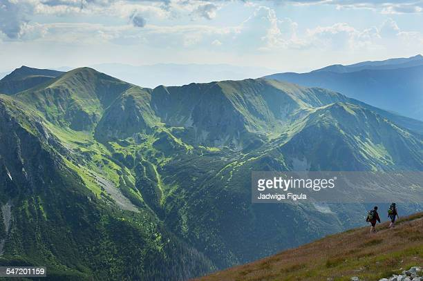 A couple hiking with backpacks along the narrow path in High Tatra Mountains in Poland.