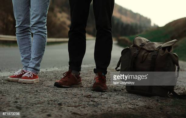 couple hitchhiking on the road - hitchhiking stock pictures, royalty-free photos & images
