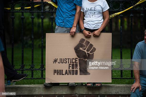 A couple hold a sign protesting the killing of Philando Castile outside the Governor's Mansion on July 7 2016 in St Paul Minnesota Castile was shot...