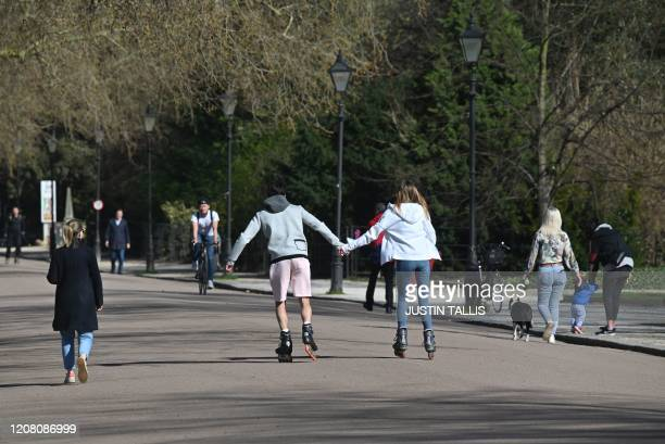 A couple hold hands as they rollerblade in Battersea Park in London on March 24 2020 after Britain's government ordered a lockdown to slow the spread...