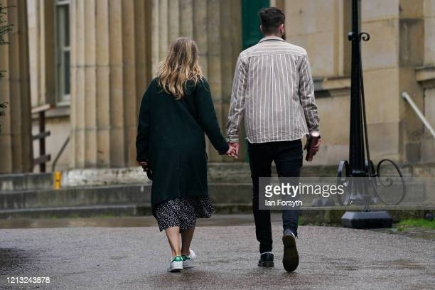 Couple hold hands as they walk through the York Museum Gardens as the UK adjusts to life under the Coronavirus pandemic on March 18, 2020 in York,...