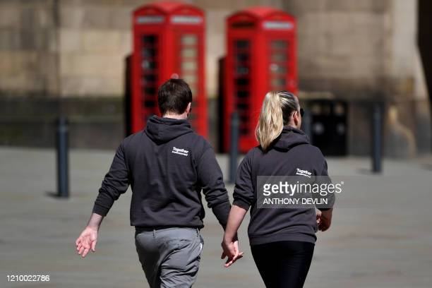 A couple hold hands as they wear jerseys reading Together We Are Sorted in St Peters Square in the neardeserted city centre of Manchester northwest...