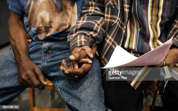 Couple hold hands at dawn, after sleeping in their cars, to see a doctor at the Remote Area Medical mobile dental and medical clinic on June 10, 2017...