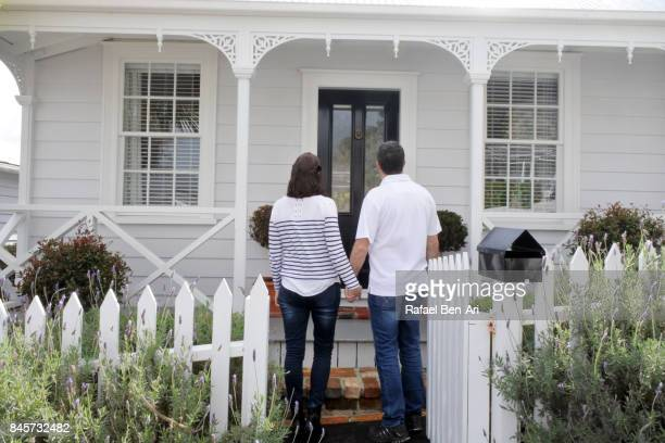 couple hold hands in front of their new home - rafael ben ari stock pictures, royalty-free photos & images