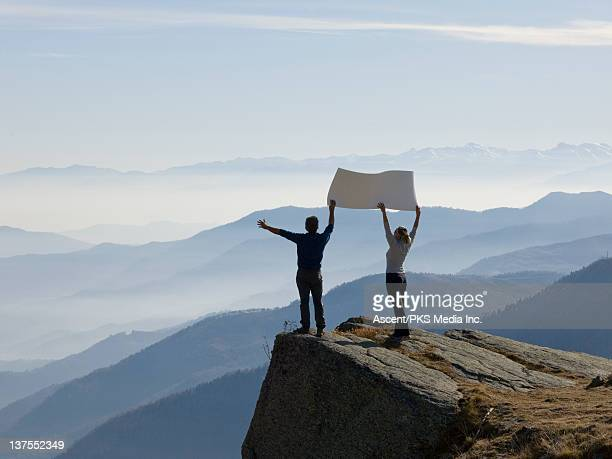 Couple hold placard hgh above distant mountains