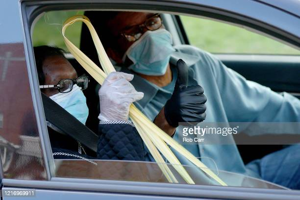 A couple hold up a palm leafs after attending a walk thru Palm Sunday Service at Friendship Baptist Church held due to the COVID19 pandemic on April...
