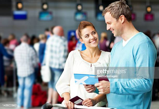 Couple tenant un poste d'impression des cartes d'embarquement