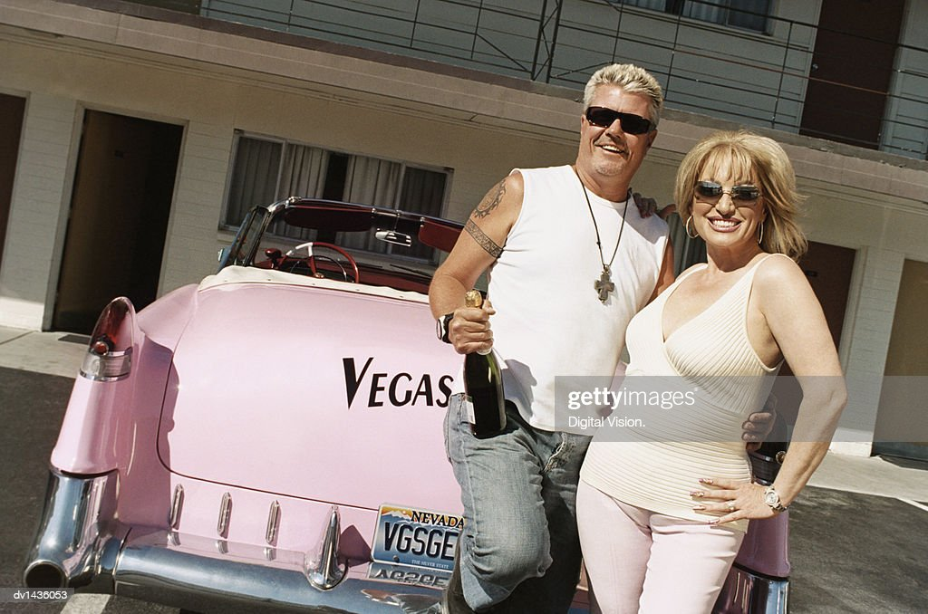 Couple Holding A Bottle Of Champagne Leaning On Pink 1950s Style Car Stock Photo