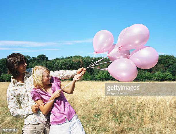 Couple holding a bunch of balloons