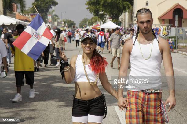 Couple holding a Dominican Republic flag at Carnival Miami.