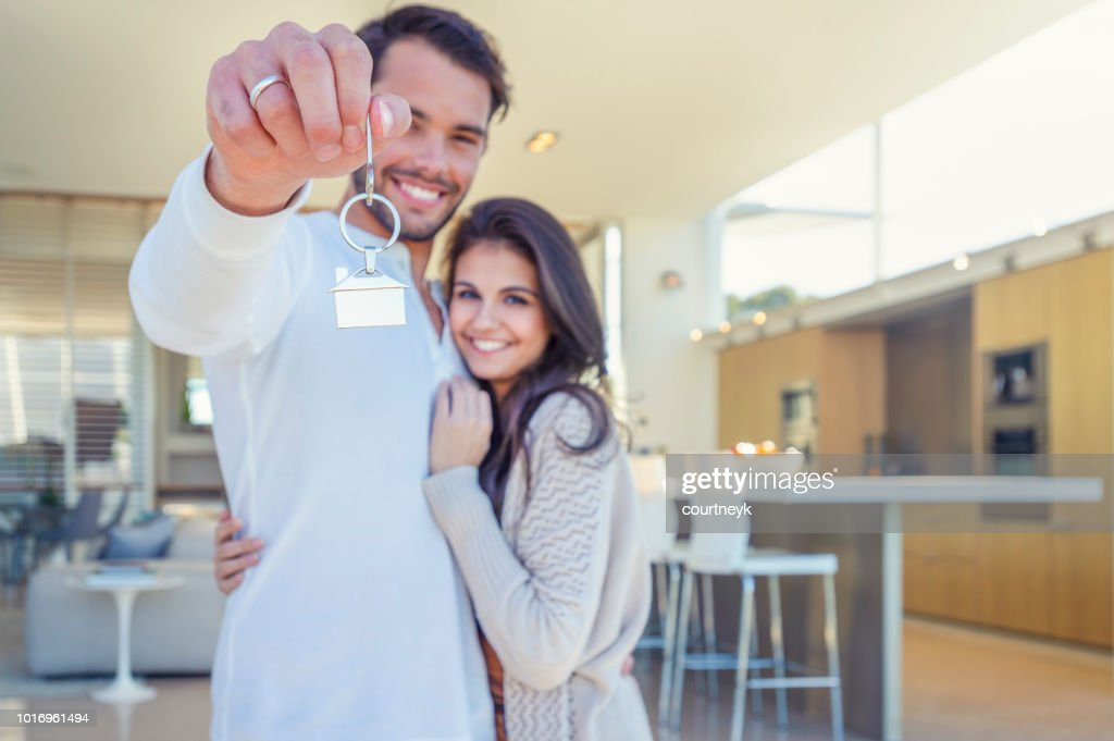 Couple holding a house key in their new home. : Stock Photo
