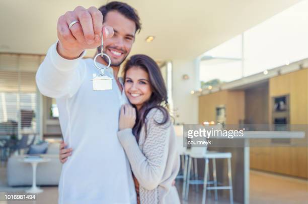 couple holding a house key in their new home. - home ownership stock pictures, royalty-free photos & images