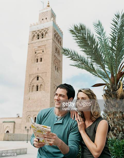 Couple Holding a Map at the Tower of Djemaa El Fna in Marrakesh, Morocco