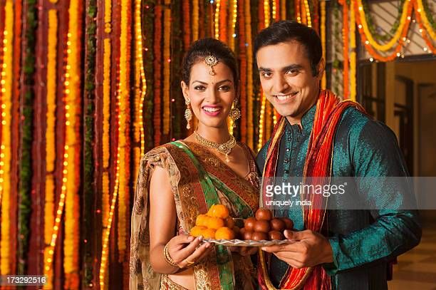 couple holding a plate of sweets on diwali - diwali sweets stock photos and pictures