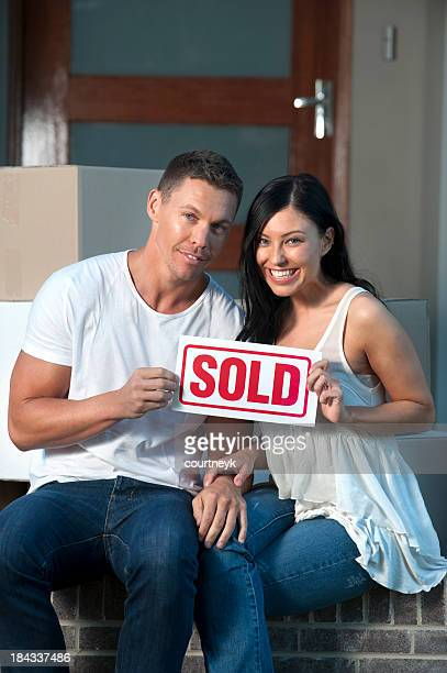 Couple tenant un panneau vendu