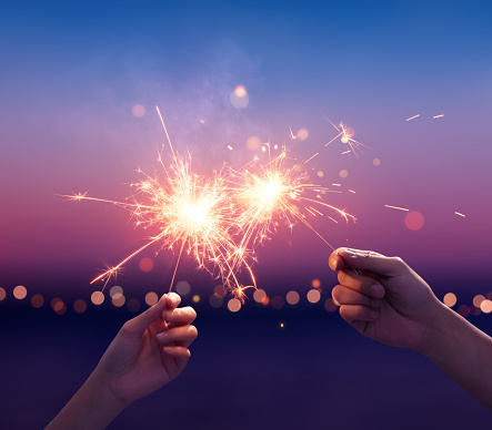 Couple holding a sparklers on the beach 1153383527