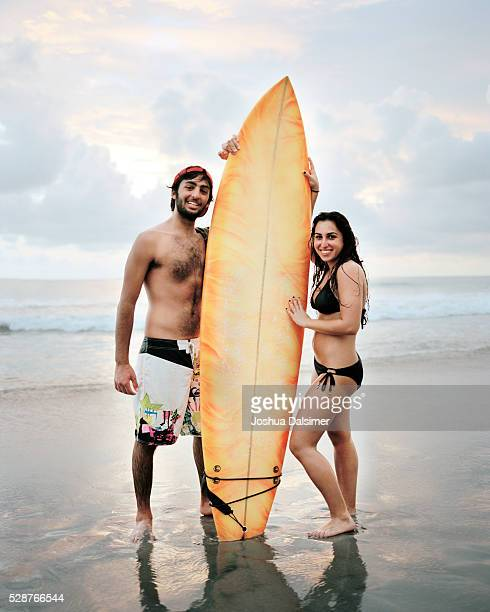 Couple holding a surfboard on the beach