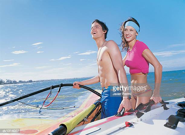 couple holding a windsurfing board in the sea - monokini photos et images de collection