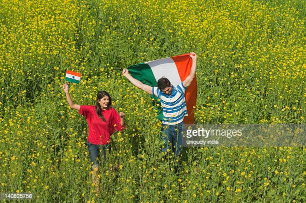 Couple holding an Indian flag and running in an oilseed rape field
