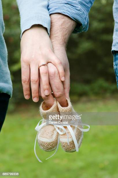 Couple holding baby booties in fingers