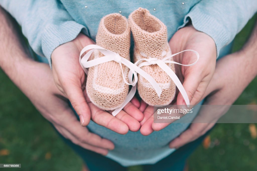 Couple holding baby booties in hands : Stock Photo