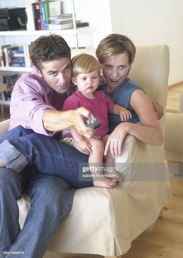 Couple holding baby, sitting on sofa : Stockfoto