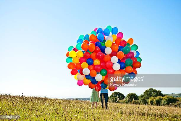 couple holding big bunch of balloons - helium balloon stock pictures, royalty-free photos & images