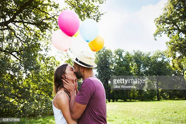 Couple holding bunch of balloons and kissing in park