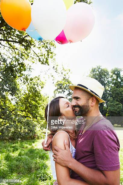 Couple holding bunch of balloons in park